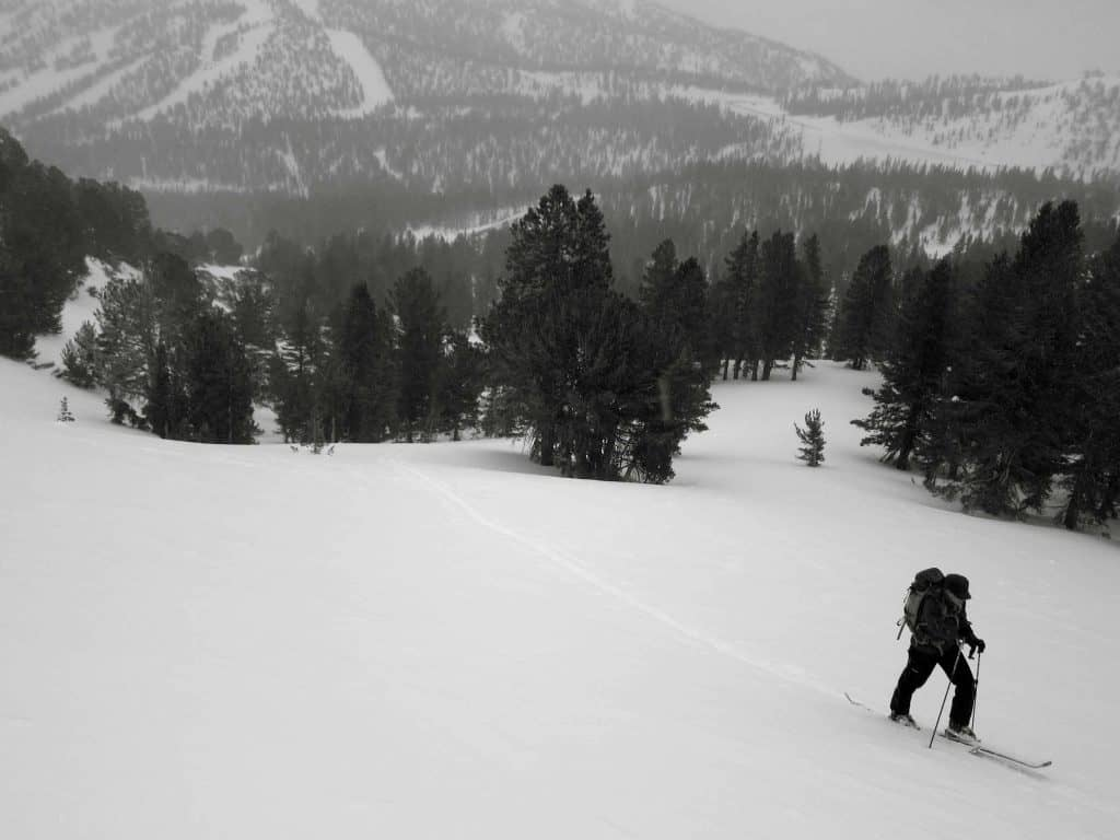 Pam skinning up under early grey skies with Mt Rose ski area in the background