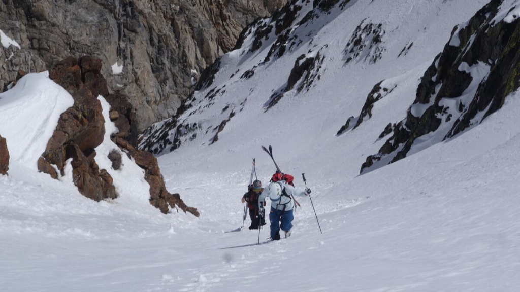 Backcountry skiers hiking up couloir