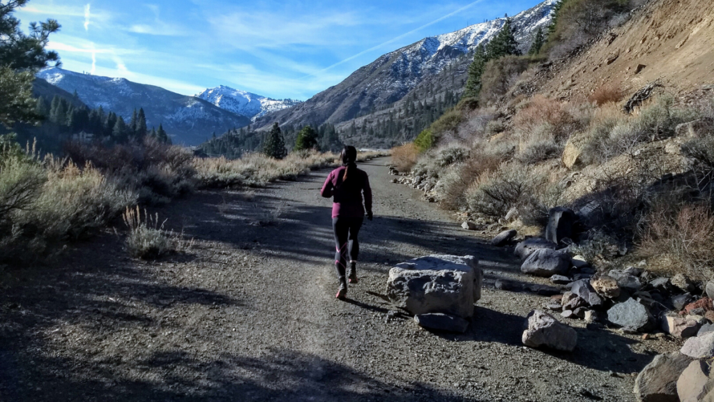 A woman running on a dirt road with mountains in the background, part of the Tahoe Pyramid Trail.